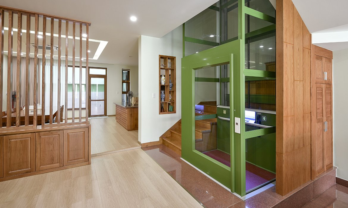 Green home lift in wooden staircase