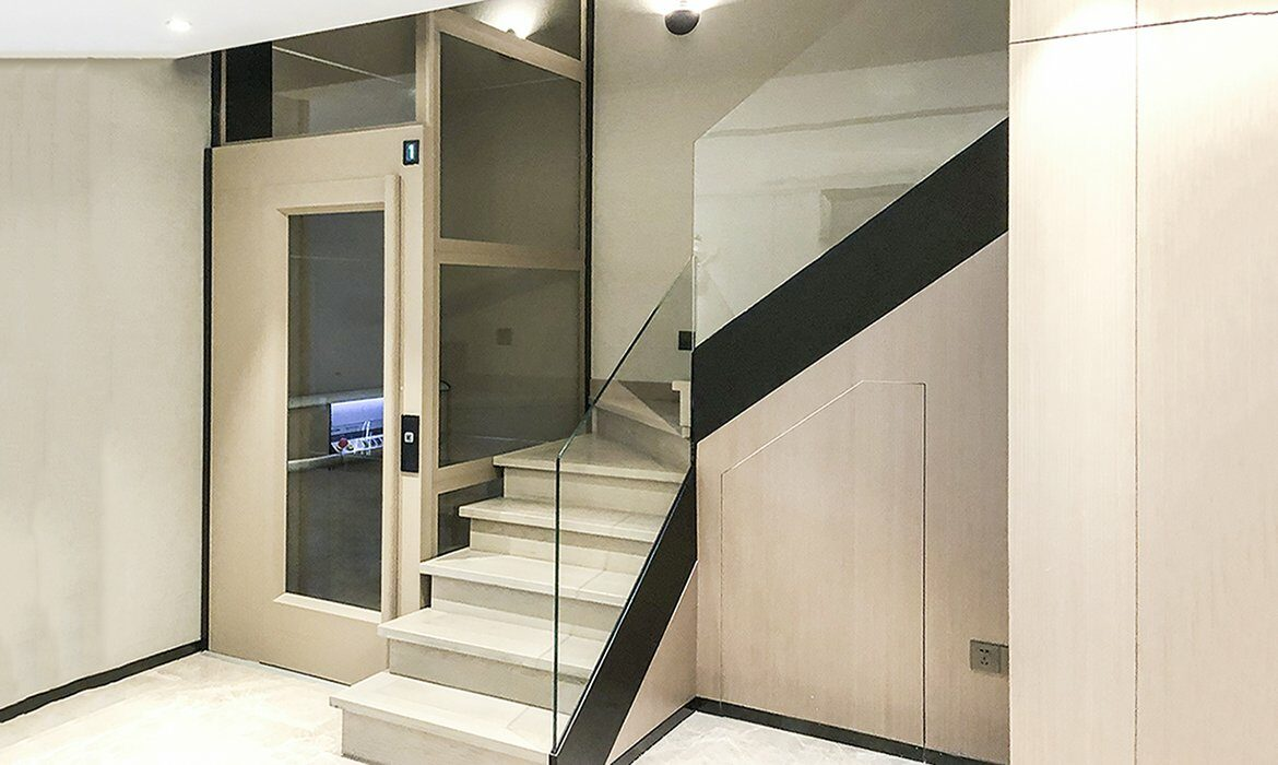 Glass lift in tinted glass placed inside staircase