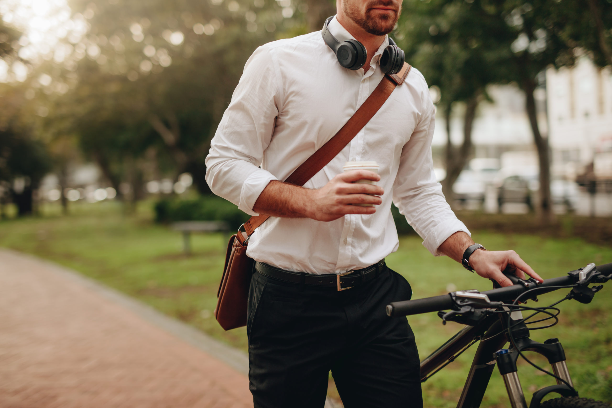 Man Cycling To Work With Coffee