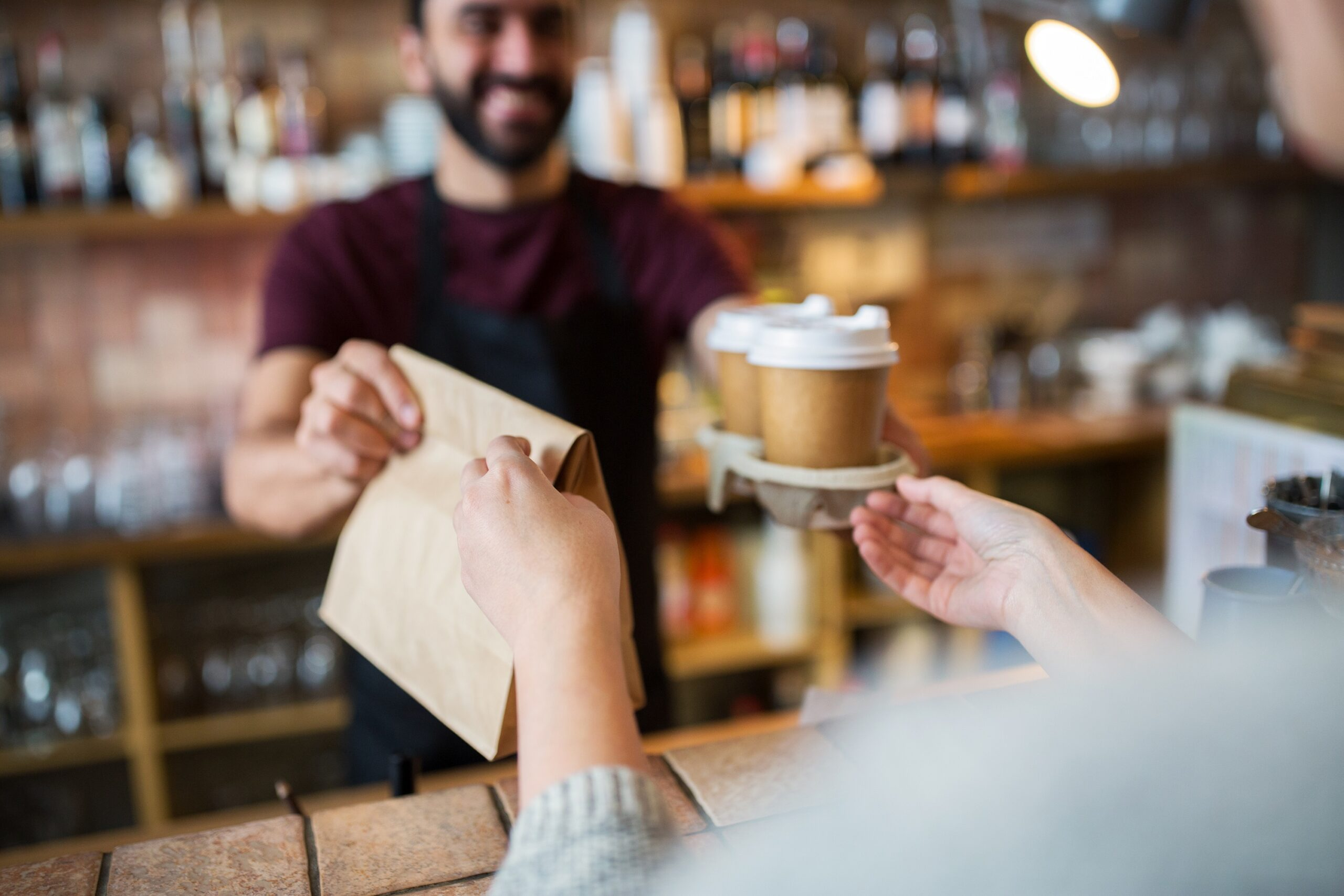Barista handing over free coffee and cake