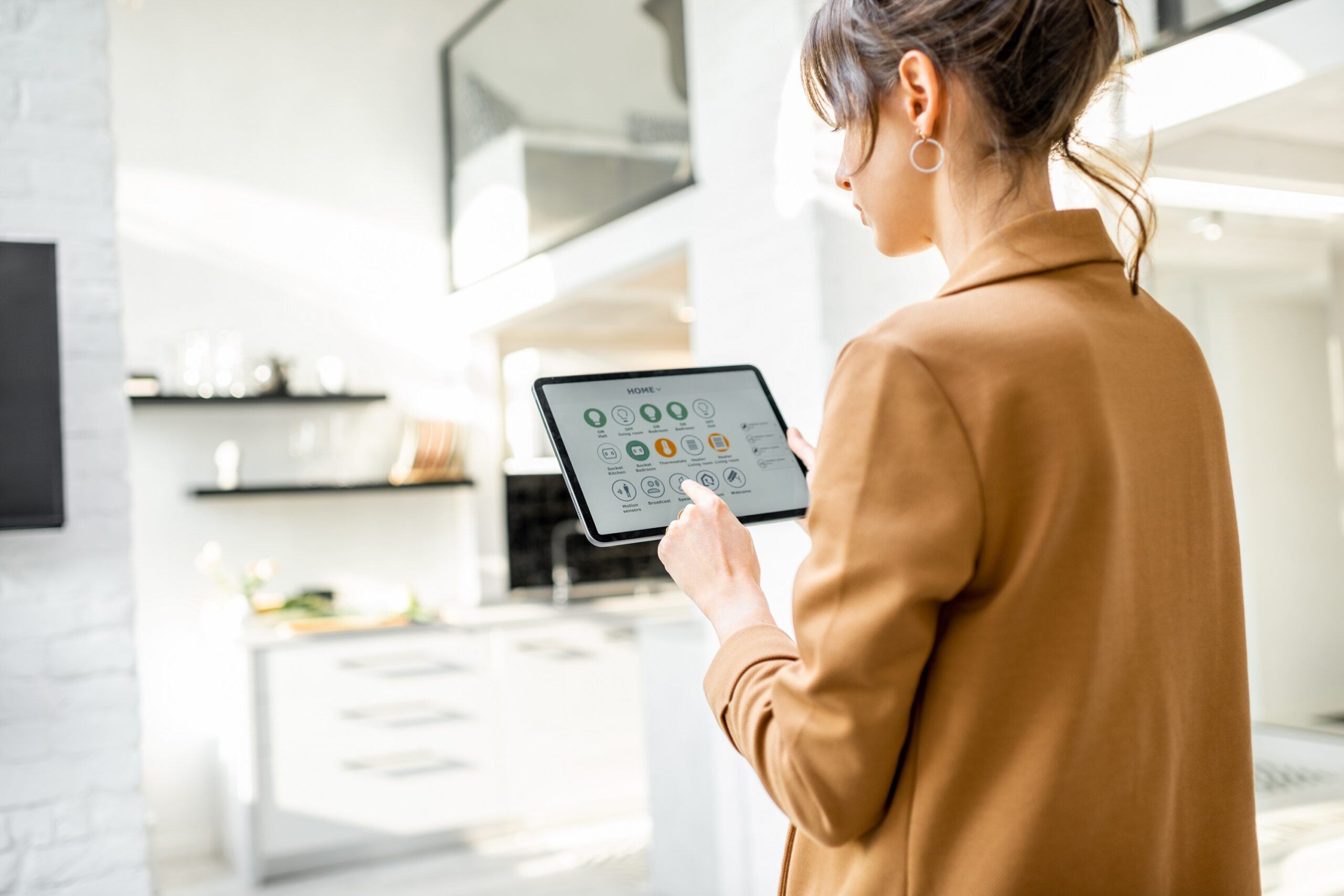 Young women controlling smart technology in home on tablet